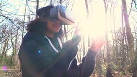 两种人种的非裔美国人的使用虚拟现实VR耳机的女孩少年女性年轻女人在森林森林地环境 股票视频