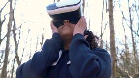 两种人种的非裔美国人的使用虚拟现实VR耳机的女孩少年女性年轻女人在森林森林地环境 股票录像