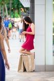 两种人种青少年在有购物袋的红色礼服外部商店 库存照片