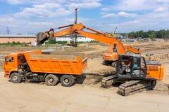 两种挖掘机装载地球入翻斗车 库存照片