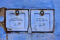 两种金属箱子和蓝色打破的墙壁 免版税库存照片