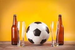 两空的杯啤酒和瓶临近足球 库存图片