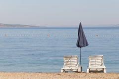 两空的轻便折叠躺椅和一把蓝色遮阳伞 免版税图库摄影
