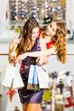 两站立与在拥抱和嘲笑购物中心的礼服的袋子的女孩 幸福概念,购物,友谊 免版税库存照片