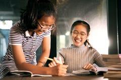 两笑激动幸福的亚裔女孩完成学校家工作在客厅 免版税库存图片