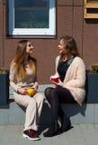 两笑年轻俏丽的妇女户外和饮用的咖啡 李 免版税图库摄影