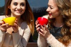 两笑年轻俏丽的妇女户外和饮用的咖啡 李 免版税库存照片
