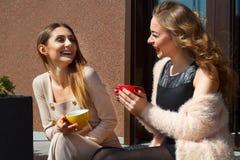 两笑年轻俏丽的妇女户外和饮用的咖啡 李 库存图片