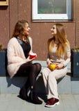 两笑年轻俏丽的妇女户外和饮用的咖啡 李 图库摄影