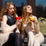 两笑年轻俏丽的妇女户外和饮用的咖啡 李 库存照片