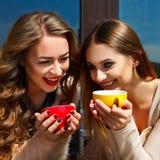 两笑年轻俏丽的妇女户外和饮用的咖啡 李 免版税库存图片
