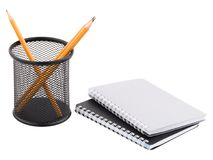 两笔记薄和在有里面锋利的铅笔的容器旁边 背景查出的白色 库存照片