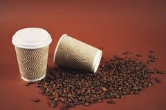两粒纸咖啡杯和豆在棕色背景 免版税库存图片