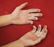 两粗砺和在红色背景的肮脏的手在上升的健身房 手在白垩和沙粒报道 库存图片