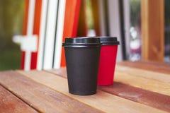 两红色和黑纸杯对在木地板上的饭菜外卖点在咖啡馆之外 水橇板立场后边在背景 库存照片