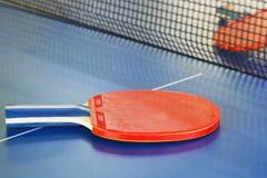 两红色在球台上的网球拍 免版税库存照片