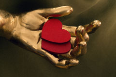 两红色心脏在金手上 库存图片
