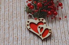 两红色心脏由木头制成在羊毛编织背景 库存照片
