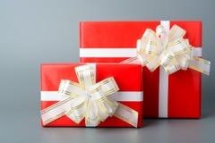 两红色有一条白色丝带和弓的礼物盒 库存图片