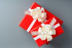 两红色有一条白色丝带和弓的礼物盒 库存照片