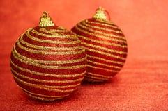 两红色有金条纹的圣诞节玩具在红色背景 库存照片
