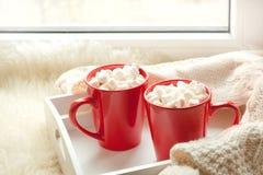 两红色杯子热巧克力用在白色窗台的蛋白软糖与毛皮为休息假日 免版税库存照片