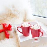 两红色杯子热巧克力用在白色窗台的蛋白软糖与毛皮为休息假日 免版税库存图片