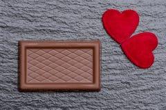 两红色蓬松心脏和巧克力混合药剂在概略的黑板岩背景服务 库存图片