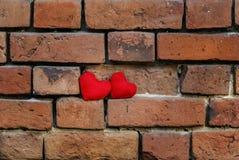 两编织了在粉碎的老红砖被构造的墙壁上的心脏 免版税图库摄影