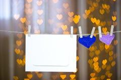 两编织了在晒衣夹的心脏和照片框架 免版税图库摄影