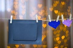 两编织了在晒衣夹的心脏和照片框架 免版税库存照片