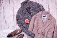 两羊毛外套,在一张白色毛皮,一半的棕色黑漆皮鞋葡萄柚,木背景 秀丽蓝色聪慧的概念表面方式构成妇女 图库摄影