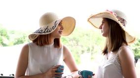 两美丽和大夏天帽子的华美的妇女显露的射击在阳台饮用的咖啡 股票视频