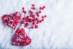 两美丽的葡萄酒红色心脏用在白色雪背景的槲寄生莓果 圣诞节、爱和圣情人节概念 免版税库存照片