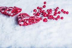 两美丽的葡萄酒红色心脏用在白色雪背景的槲寄生莓果 圣诞节、爱和圣情人节概念 免版税图库摄影