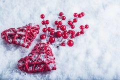 两美丽的葡萄酒红色心脏用在白色雪背景的槲寄生莓果 圣诞节、爱和圣情人节概念 免版税库存图片