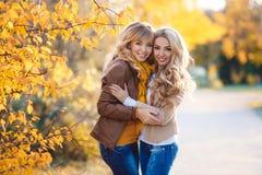 两美丽的金发碧眼的女人在秋天公园 免版税图库摄影
