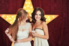 两美女读了在电话和笑的一则消息 库存图片