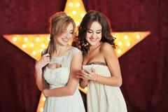两美女读了在电话和笑的一则消息 免版税库存照片