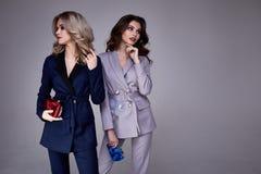 两美好的魅力性感的妇女朋友同事穿戴正式博士 免版税库存图片