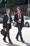 两聊天的商人,穿过街道 图库摄影