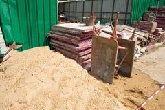 两肮脏的独轮车、沙子和建筑器材在建造场所 免版税库存照片