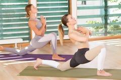 两舒展在健身房的年轻运动的妇女 库存照片