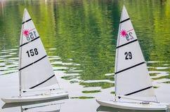两艘浮动玩具帆船在池塘 免版税图库摄影