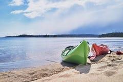 两艘皮船在湖的含沙岸停泊了,背景的 库存照片