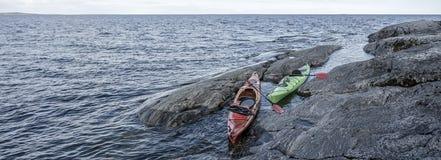 两艘皮船在湖的岩石岸停放了 全景 图库摄影