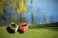 两艘皮船说谎在草的一棵树下在湖的岸, 免版税库存照片