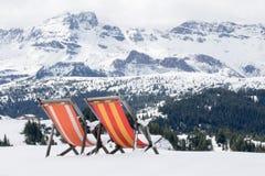 两色的deckchairs在新鲜的雪被安装 库存图片