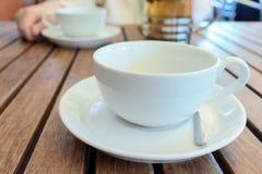 两茶杯和法语在桌,被弄脏的妇女上按后边 免版税库存照片