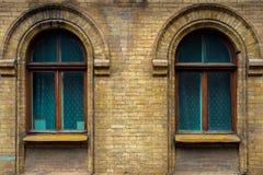两葡萄酒成拱形在黄色砖墙壁的窗口  绿色-海在一褐红深红木的波浪玻璃的颜色 库存照片